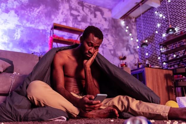 Brudny dywan. zmęczony i zdezorientowany mężczyzna siedzi na podłodze przykryty czarnym kocem i sprawdza smartfon