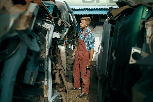 Brudny mechanik wybiera części zamienne na złomowisku samochodów. złom samochodowy, śmieci samochodowe, śmieci samochodowe, porzucony, uszkodzony i zgnieciony transport
