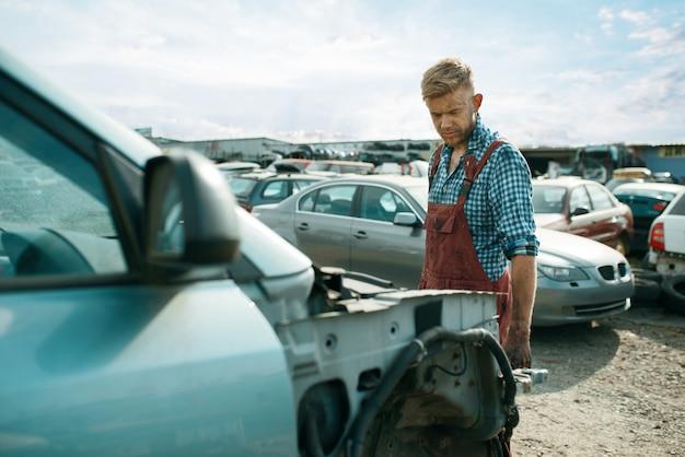 Brudny mechanik wybiera części zamienne na złomowisku samochodów