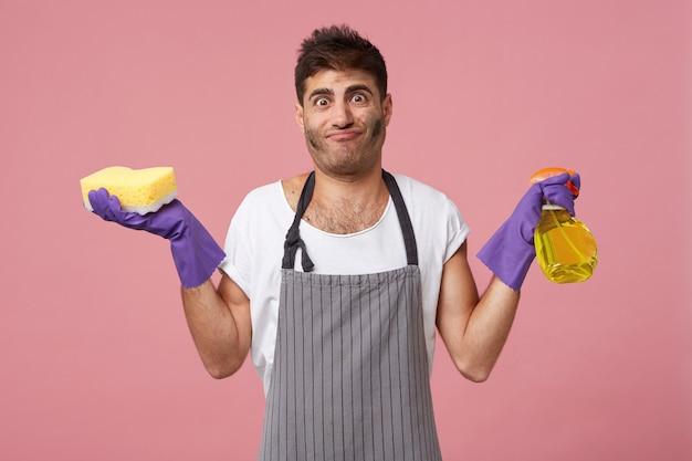 Brudny mężczyzna ze stylową fryzurą i włosiem trzymającym gąbkę i detergent w zwykłej białej koszulce, fartuchu i rękawiczkach, który jest zmęczony