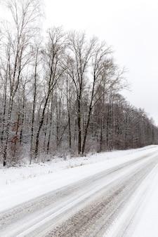Brudny śnieg pokrywający drogę asfaltem, zbliżenie fotografii w zimie