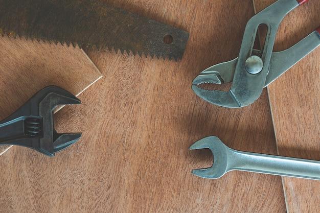 Brudny zestaw narzędzi ręcznych na drewnianym tle stary zardzewiały sprzęt do sklepu ślusarskiego i obróbki metali stary sklep stare narzędzia pracy. vintage narzędzia robocze wiertła linijka piły i inne na drewnianym tle