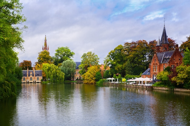 Brugia, flandria, belgia, europa - 1 października 2019 r. neogotycki średniowieczny zamek nad brzegiem jeziora miłości jesienią brugia (brugge)