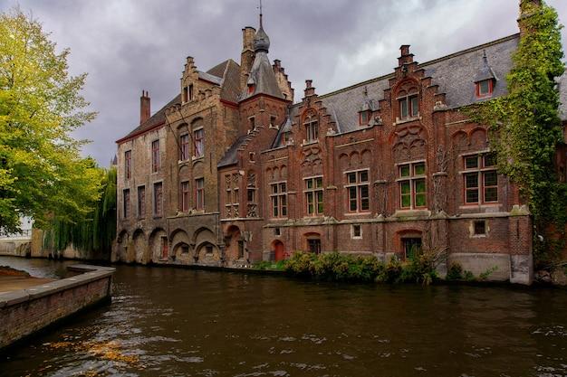 Brugia, flandria, belgia, europa - 1 października 2019 r. średniowieczne starożytne domy zbudowane ze starych cegieł i kanałów wodnych jesienią brugia (brugge)