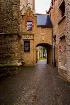 Brugia, flandria, belgia, europa - 1 października 2019 r. średniowieczne starożytne domy ze starych cegieł na starożytnej średniowiecznej ulicy w brugii (brugge)
