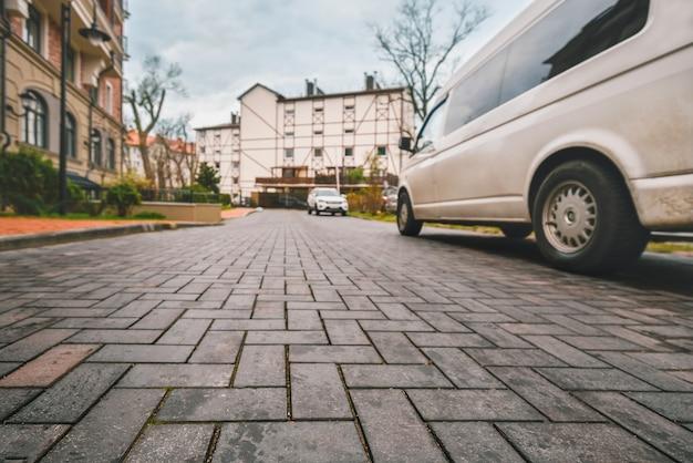 Bruk, typowa europejska ulica, rząd niskich domów mieszkalnych, rząd samochodów, widok z dołu