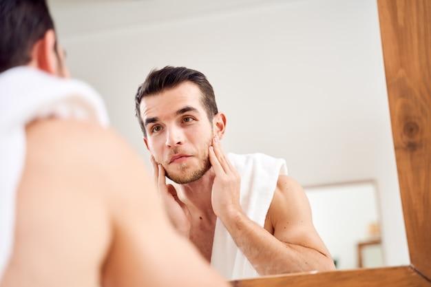 Brunet myje twarz i stoi z ręcznikiem na ramionach przed lustrem w łazience