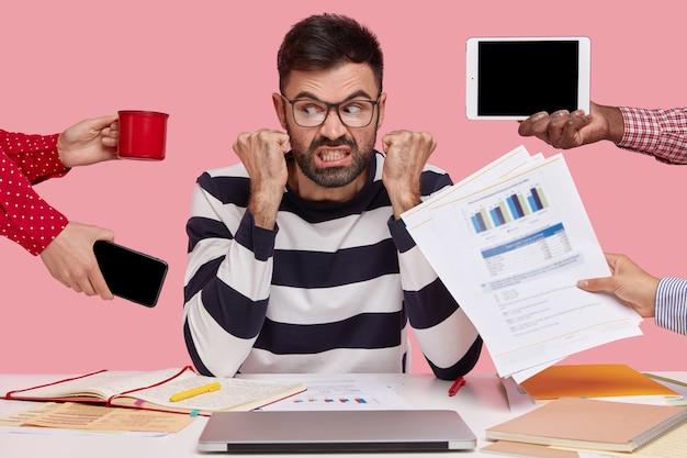 Brunet siedzący przy biurku otoczony gadżetami i papierami