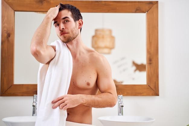 Brunet z białym ręcznikiem na ramieniu stojący przy lustrze w wannie