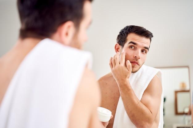 Brunet z ręcznikiem na ramionach i słoikiem z kremem w dłoniach stoi rano przed lustrem w łazience