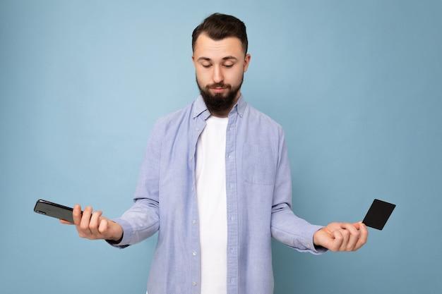 Brunet zarośnięty młody człowiek ubrany w dorywczo niebieską koszulę i biały t