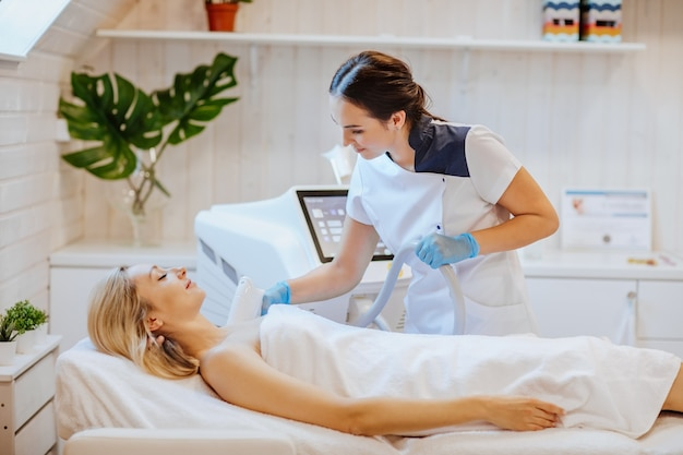 Brunetka atrakcyjna lekarz trzyma maszynę do depilacji i używa jej na ciele kobiety.