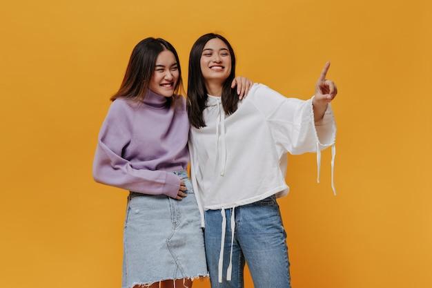 Brunetka azjatycka kobieta w dżinsach i białej bluzie z kapturem, uśmiecha się, przytula swoją dziewczynę i wskazuje na miejsce na tekst na izolowanej pomarańczowej ścianie