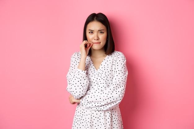 Brunetka azjatycka kobieta w sukience wygląda na niezadowoloną, marszcząc brwi i zapinając usta, pieczęć usta z obietnicą, stojąc na różowym tle.