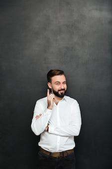 Brunetka biznesmen pozuje na kamerze z chytrym szczęśliwym spojrzeniem, wskazuje palec wskazującego, jakby wiedział coś nad ciemnoszarym