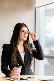 Brunetka bizneswoman jest ubranym szkła