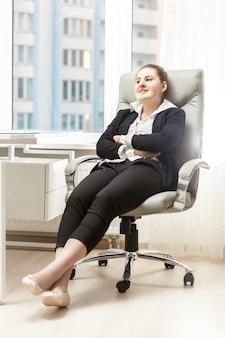 Brunetka bizneswoman relaksuje się w skórzanym fotelu w biurze