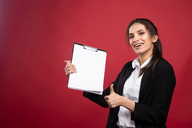 Brunetka bizneswoman trzyma schowek i daje kciuki do góry.
