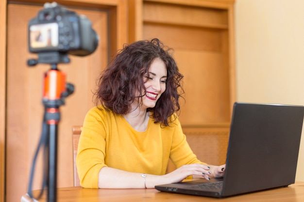 Brunetka blogerka pisze na laptopie