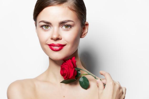 Brunetka czerwone usta uśmiechać się czystą skórę zabiegi spa kwiat jasny makijaż tło