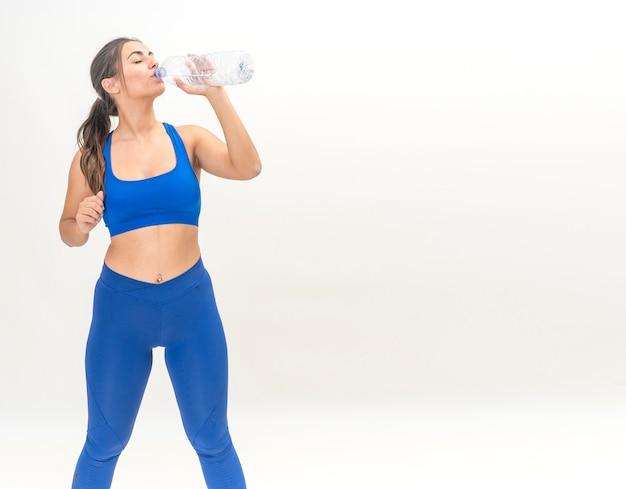 Brunetka dama ćwiczenia fitness, aby schudnąć i wody pitnej w butelce