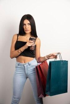 Brunetka dama trzyma kawę i torby na zakupy. wysokiej jakości zdjęcie