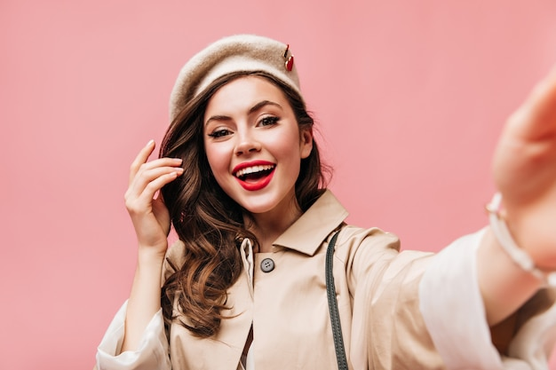 Brunetka dama w beżowym berecie uśmiecha się i robi selfie na różowym tle.