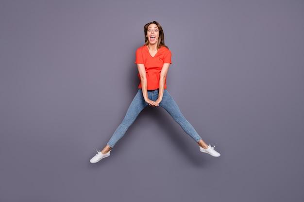 Brunetka dama w czerwonej koszulce, pozowanie i skoki na fioletowej ścianie