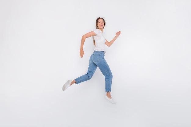 Brunetka dama w okularach pozowanie i skoki na białej ścianie