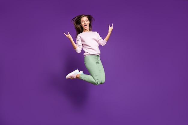 Brunetka dama w pastelowym swetrze pozuje na fioletowej ścianie