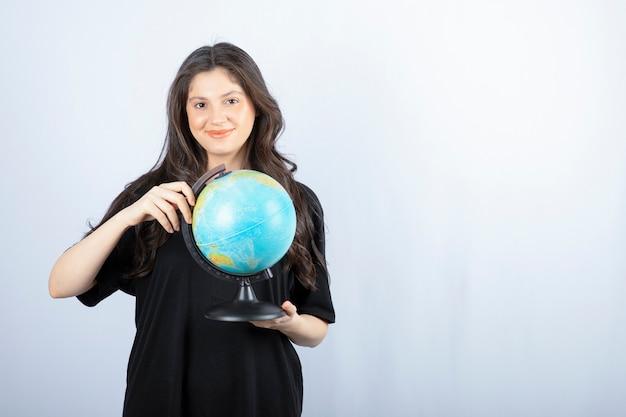 Brunetka dama z długimi włosami, trzymając światową kulę ziemską i pozowanie.