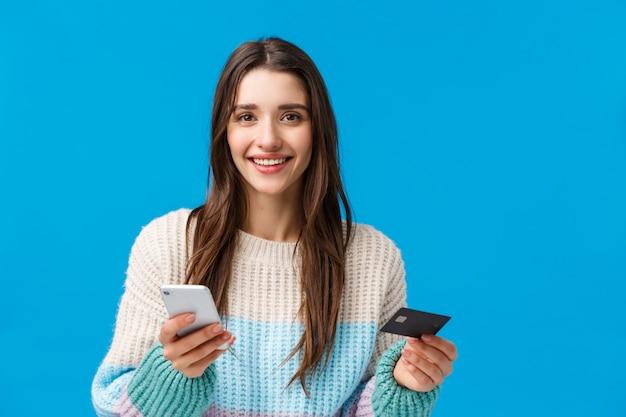 Brunetka dama z zimowym swetrze posiadania karty kredytowej i telefonu komórkowego