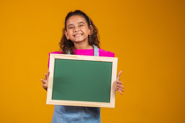 Brunetka dziecko trzyma tablicę na żółtym tle.