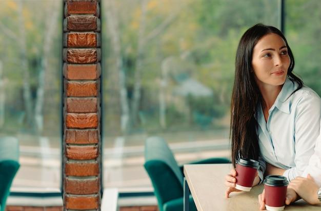 Brunetka dziewczyna odpoczywa i pije kawę w przerwie na kawę pracy. koncepcja odpoczynku w kawiarni w przerwie między pracą.