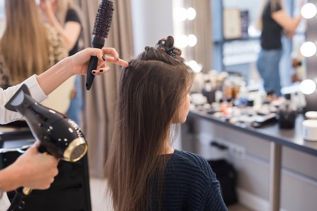 Brunetka dziewczyna robi jej włosy robić