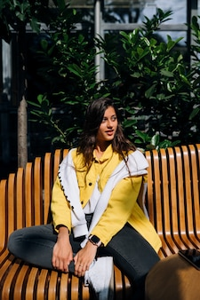 Brunetka dziewczyna siedzi na ławce w centralnej części starego miasta.