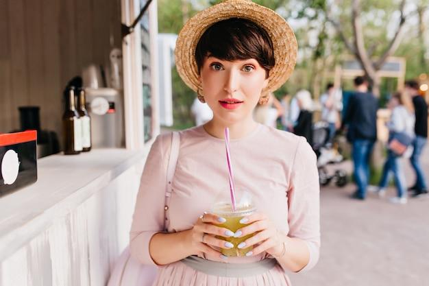 Brunetka dziewczyna stoi w słomkowym kapeluszu z wyrazem twarzy zaskoczony trzymając szklankę zielonego koktajlu