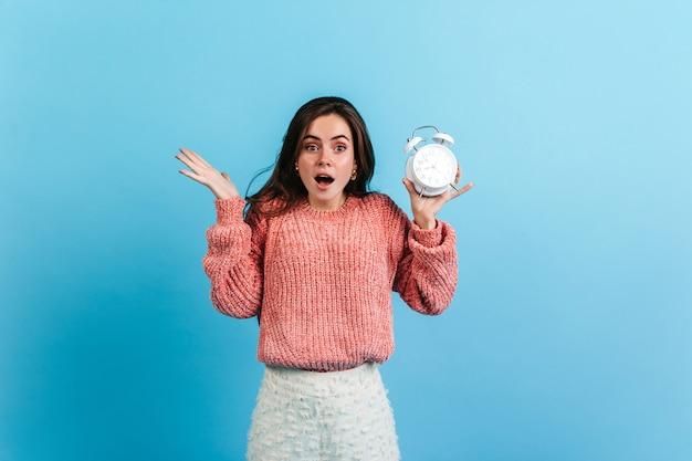 Brunetka dziewczyna trzyma budzik na niebieskiej ścianie.