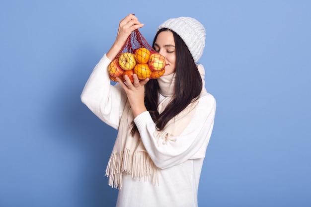 Brunetka dziewczyna trzyma worek sznurkowy z jabłkami i mandarynką