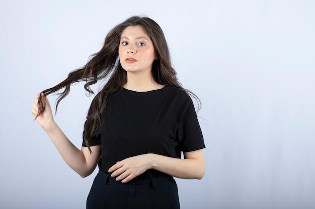 Brunetka dziewczyna w czarnej górze patrząc na kamery na białej ścianie.