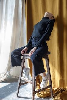 Brunetka dziewczyna w czarnym golfie i dżinsach siedzi na stołku, bez twarzy