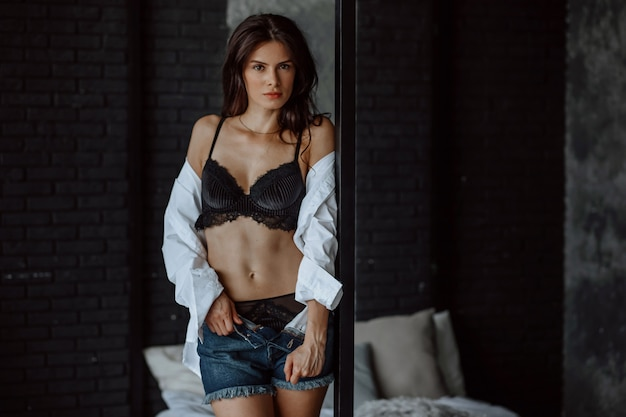 Brunetka dziewczyna w czarnym staniku stoi przy łóżku
