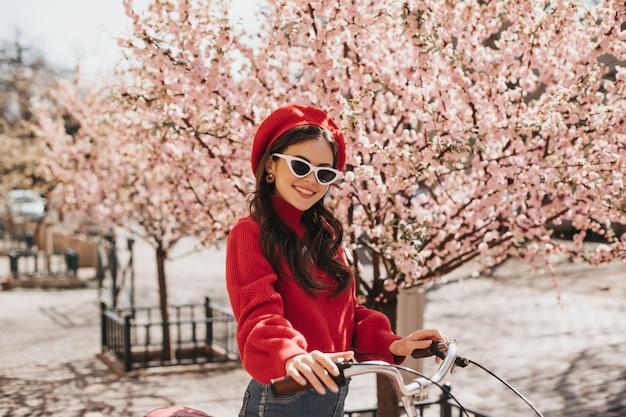 Brunetka dziewczyna w czerwonym kapeluszu i swetrze, pozowanie na tle sakury. urocza kobieta to stylowe okulary przeciwsłoneczne, uśmiechnięta i jeżdżąca na rowerze