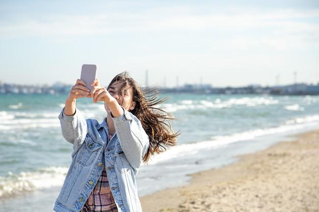 Brunetka dziewczyna w dżinsowej kurtce robi zdjęcie telefonem z aparatem selfie przed ścianą morza. pojęcie podróży i nowych doświadczeń.