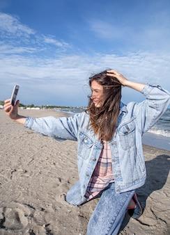 Brunetka dziewczyna w dżinsowej kurtce robi zdjęcie w aparacie telefonu. koncepcja podróży i nowych doświadczeń.