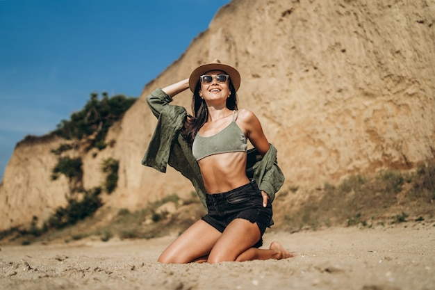Brunetka dziewczyna w kapeluszu relaks na plaży ze skałami