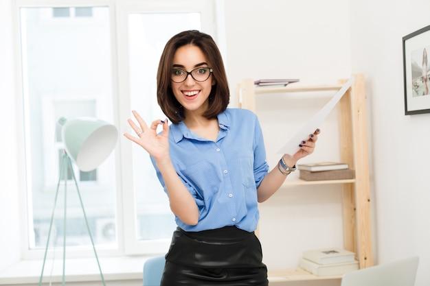 Brunetka dziewczyna w niebieskiej koszuli i czarnej spódnicy stoi w biurze. w ręku trzyma papier. uśmiecha się do kamery i robi znak w porządku.