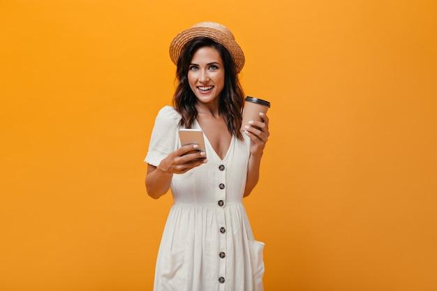Brunetka dziewczyna w słomkowym kapeluszu, trzymając smartfon i szklankę kawy. kobieta z falowanymi włosami patrzy na aparat z telefonem i szklanką herbaty w dłoniach.