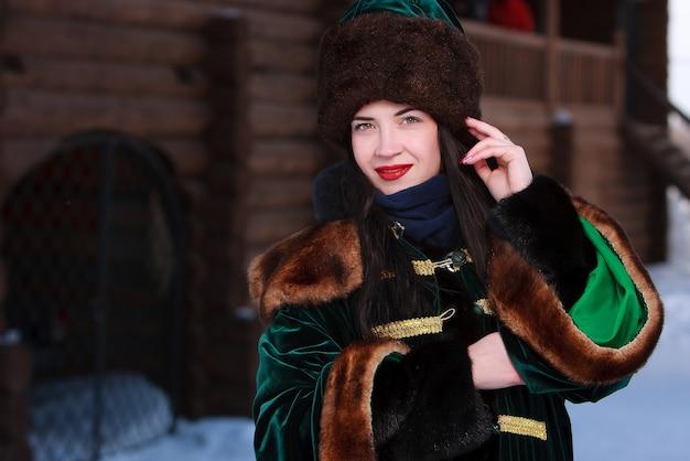 Brunetka dziewczyna w średniowiecznym rosyjskim stroju odkrytym z drewnianym zabytkowym budynkiem na tle