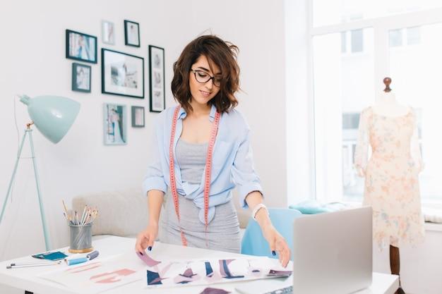 Brunetka dziewczyna w szarej sukience i niebieskiej koszuli stoi przy stole w pracowni warsztatowej. ma wiele kreatywnych rzeczy na stole. szuka próbek materiałów.